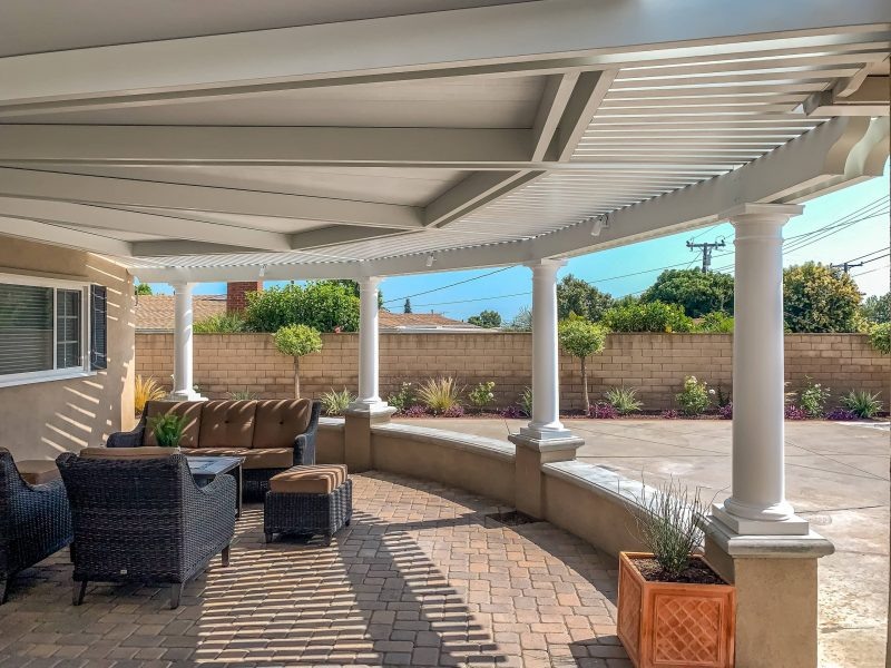 Interior perspective of a round, radiused Combination Open Lattice & Solid Insulated Patio Cover with Roman Endurastone Columns with patio furniture underneath, facing the home.
