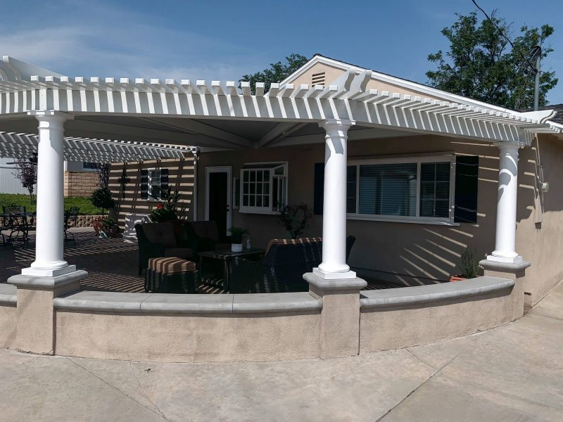 Exterior perspective of a round, radiused Combination Open Lattice & Solid Insulated Patio Cover with patio furniture underneath, facing the home.