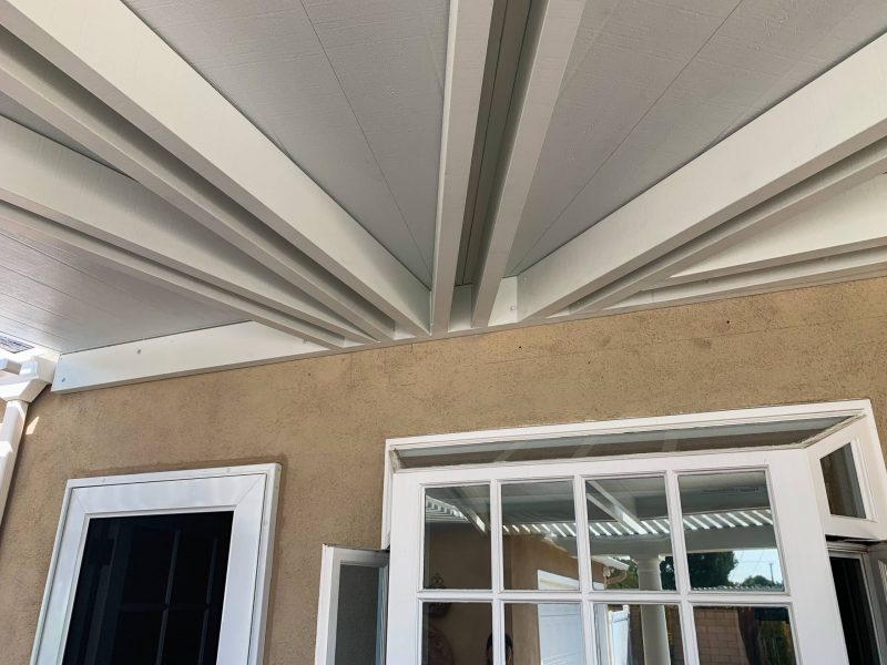 Underside of Solid Insulated Patio Cover showing 4 sets of custom double rafter beam detail coming out from the fascia beam on the house wall.