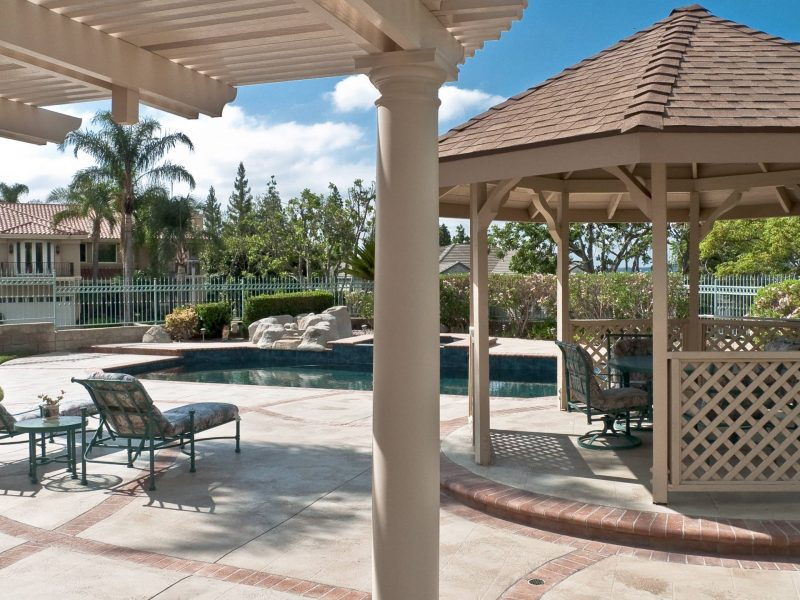 Underside of an Open Lattice Patio Cover showing a detail of a Roman Column with a Freestanding Gazebo and pool in the background in Orange County, CA