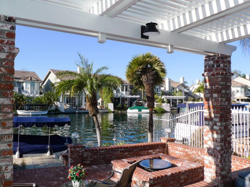 Underside of an Open Lattice Patio Cover with brick columns facing out over a canal with boats and boat docks on neighboring backyards.