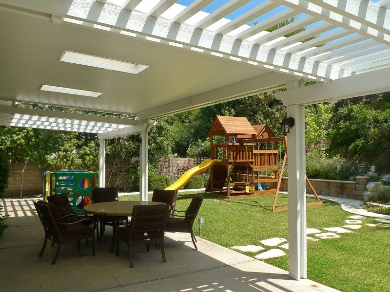 Underside of a Combination Open Lattice & Solid Insulated Patio Cover with 2 Skylights and LED lights on posts looking out at a backyard with a playground set.
