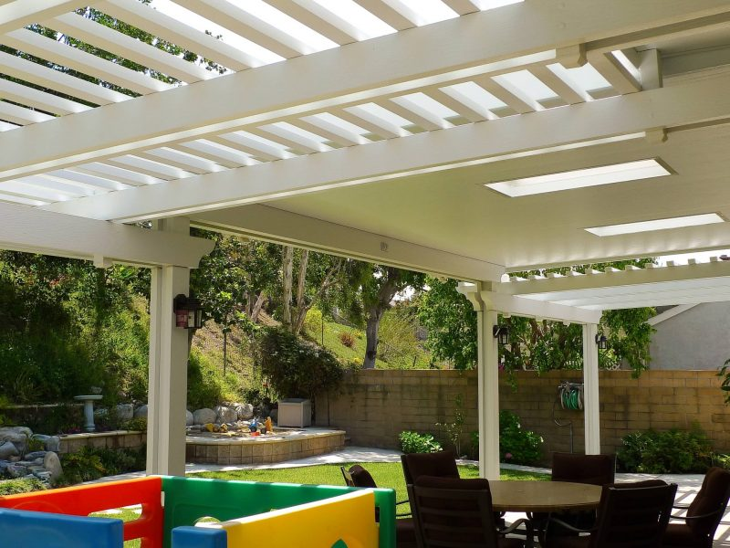 Underside of a Combination Open Lattice & Solid Insulated Patio Cover with 2 Skylights and LED lights on posts looking out at a backyard garden.