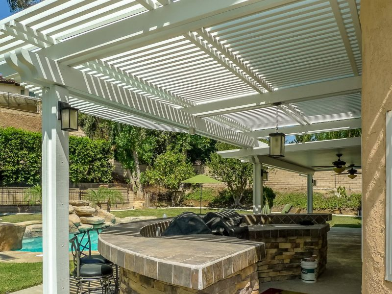 Underside of a Combination Open Lattice & Solid Insulated Patio Cover with 2 Ceiling Fans and LED lights on posts looking out at a pool.