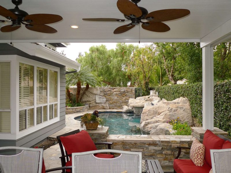 Underside of a Solid Insulated Patio Cover with 2 Ceiling Fans, LED lights and furniture, facing a pool in Dove Canyon, CA