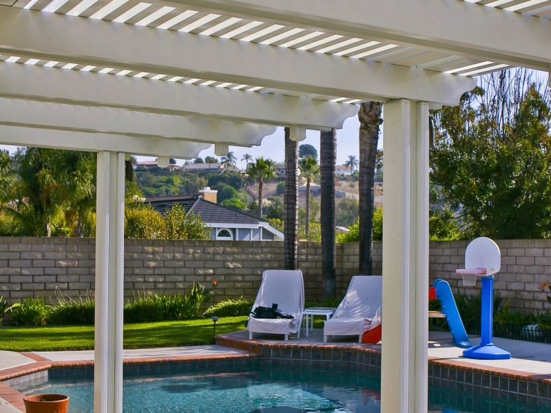 Underside of a Combination Open Lattice and Solid Insulated Patio Cover facing a pool in the backyard