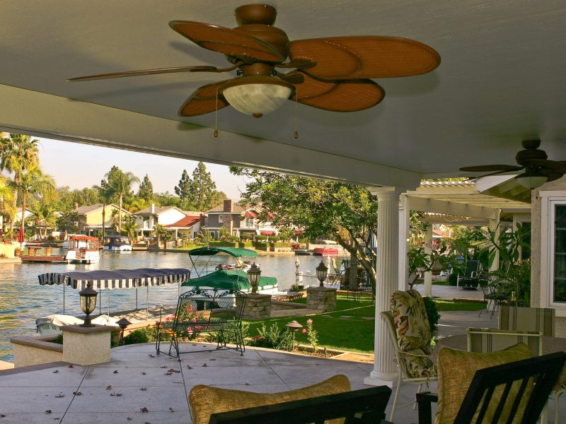 Underside of a Solid Insulated Patio Cover with 2 Ceiling Fans, Roman columns and furniture, facing a lake in Lake Forest, CA