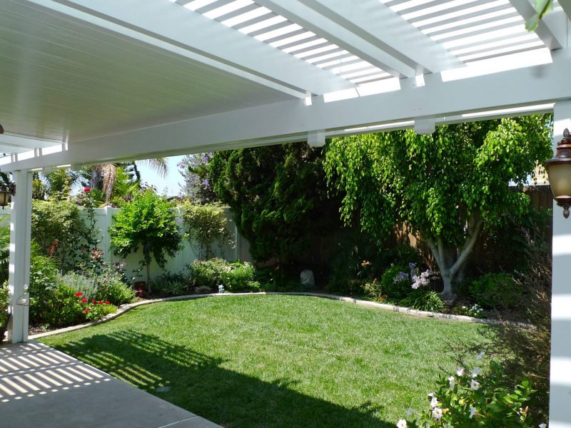 Underside of a Combination Open Lattice & Solid Insulated Patio Cover with an LED light, looking out into a backyard.