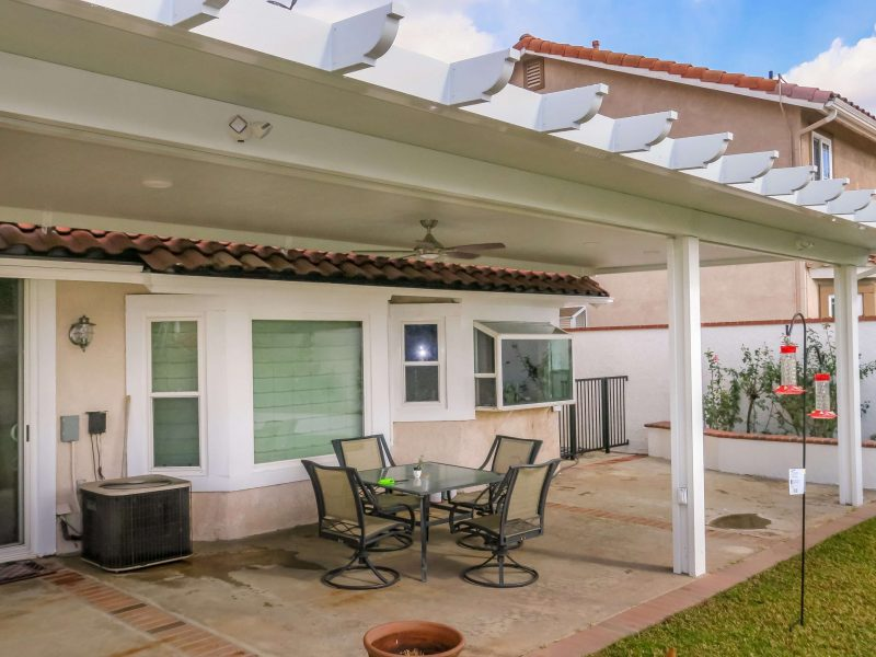 Exterior of a Solid Insulated Patio Cover with a Ceiling Fan and furniture facing customer's home in Yorba Linda, CA