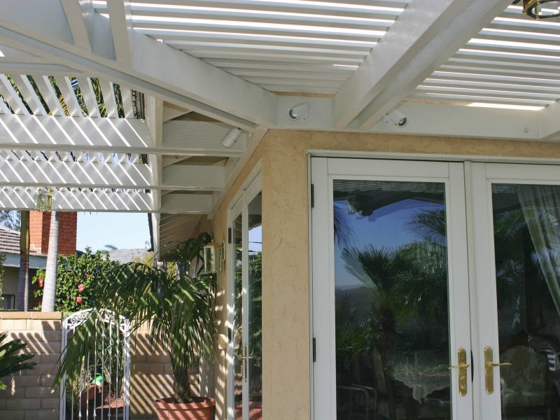Underside of an Open Lattice Patio Cover showing details of LED lights and an intricate rafter design in Orange County, CA