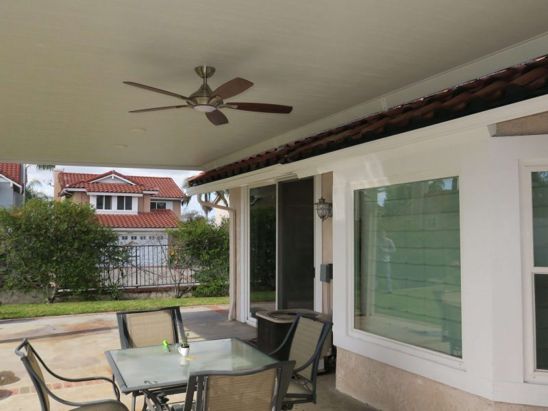 Underside of a Solid Insulated Patio Cover with LED Lights, a ceiling fan and patio furniture in Brea, CA