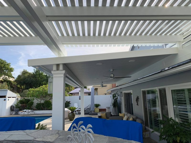 Underside of a Combination Open Lattice & Solid Insulated Patio Cover with 2 Ceiling Fans & 2 LED lights and a ceiling fan, looking out over a pool in a backyard.