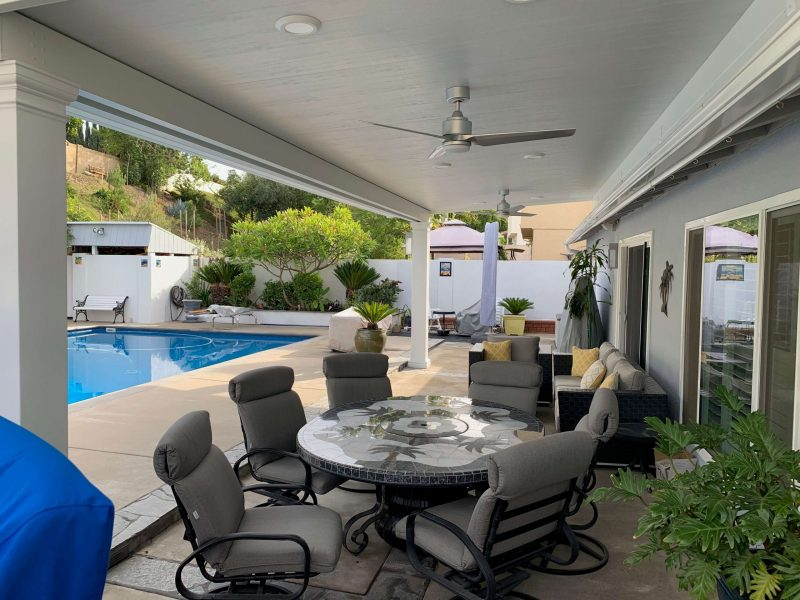 Underside of a Solid Insulated Patio Cover with 2 Ceiling Fans, LED Lights, Square Columns and Patio Furniture in Long Beach, CA