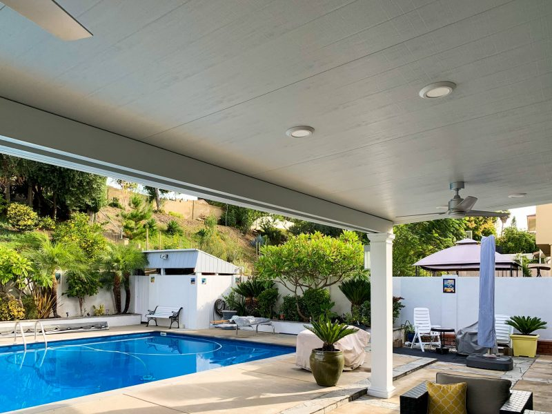 Underside of a Combination Open Lattice & Solid Insulated Patio Cover with inset LED Lights and a Ceiling Fan, looking out over a pool in a backyard