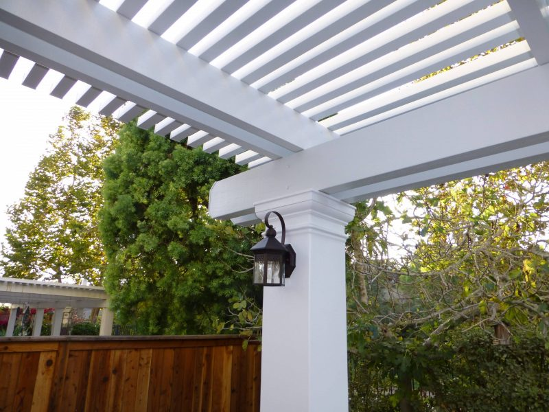Underside of an Open Lattice Patio Cover showing a detail of an LED light on a post in Orange, CA