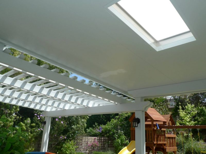 Underside of a Combination Open Lattice & Solid Insulated Patio Cover with 2 LED lights and skylight, looking out over a playground in a backyard.