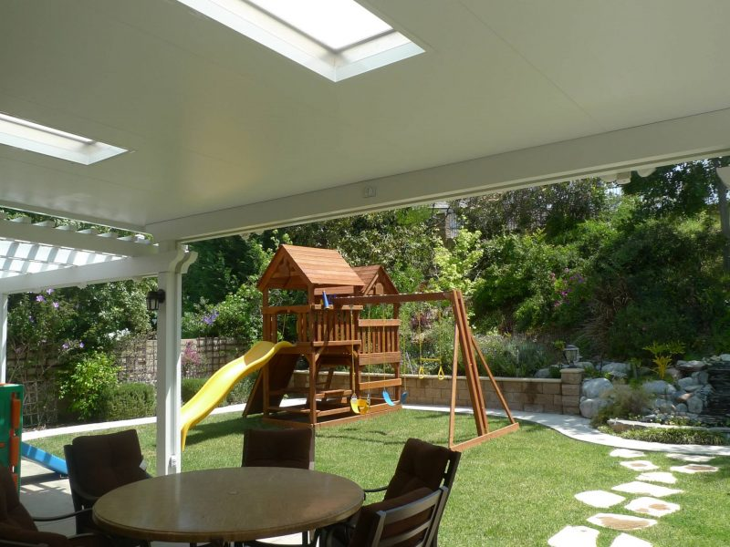 Underside of a Combination Open Lattice & Solid Insulated Patio Cover with LED lights and skylights, looking out over a playground in a backyard.