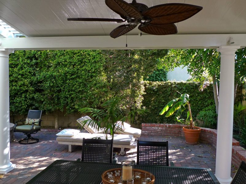 Underside of Combination Open Lattice & Solid Insulated Patio Cover showing LED lights, Roman columns and ceiling fan, looking out a backyard with patio furniture in Irvine, CA