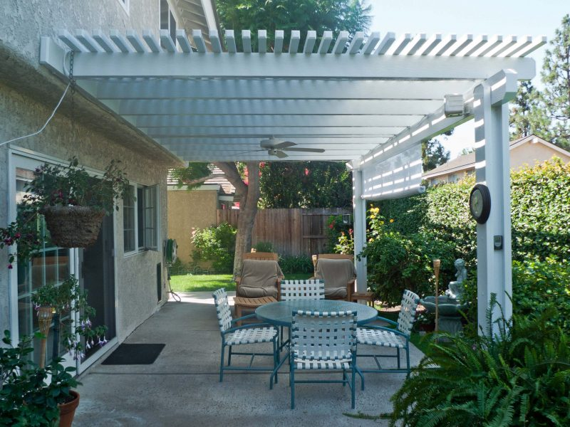 Exterior of an Open Lattice Patio Cover with Ceiling Fan, LED Lights & Drop Shade in Irvine, CA