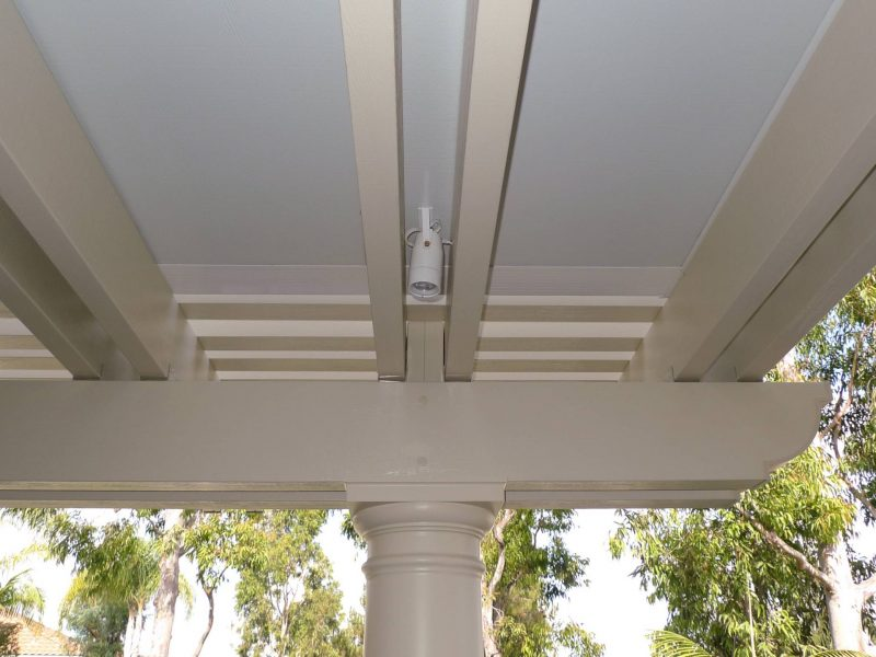 Underside of a Combination Open Lattice & Solid Insulated Patio Cover showing an up close detail of an LED light situated between 2 rafters in Rancho Santa Margarita, CA