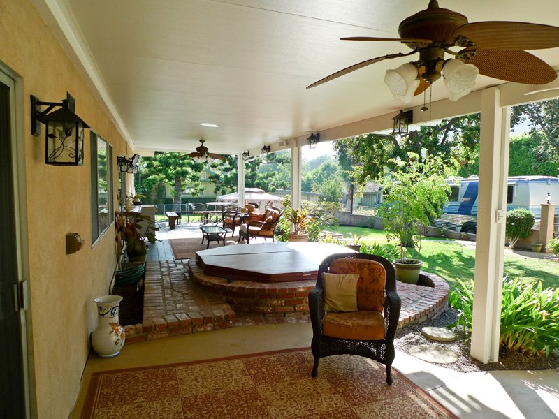 Solid Insulated Patio Cover in Santa Ana, CA with Lights & Ceiling Fans covering a Jacuzzi Hot Tub